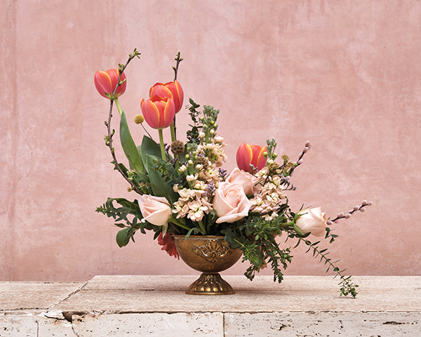 Spring floral bouquet in golden vase on marble table